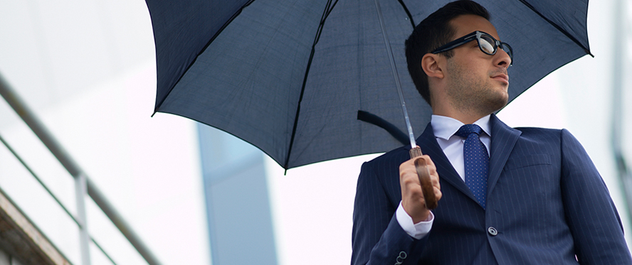 Man in a suit and sunglasses holding an umbrella