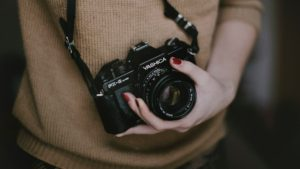Female photographer cupping the lens of her camera