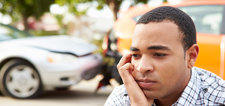 Man with hand on cheek looking pensive. The background shows a rear-end auto accident.