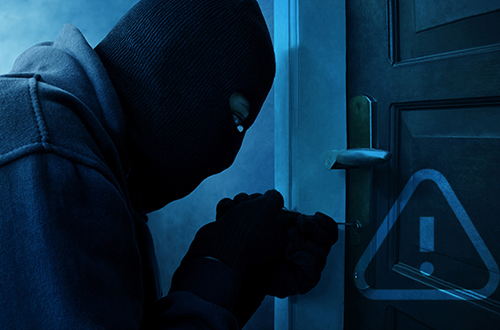 Burglar with full head mask picking at a door lock