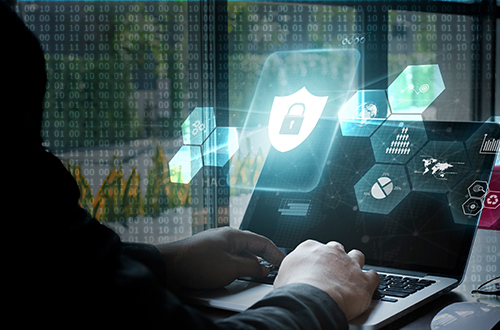Man on laptop with graphics depicting cybersecurity superimposed