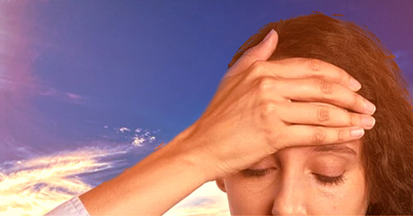 Woman with her hand over her forehead with the sun and blue sky in the background